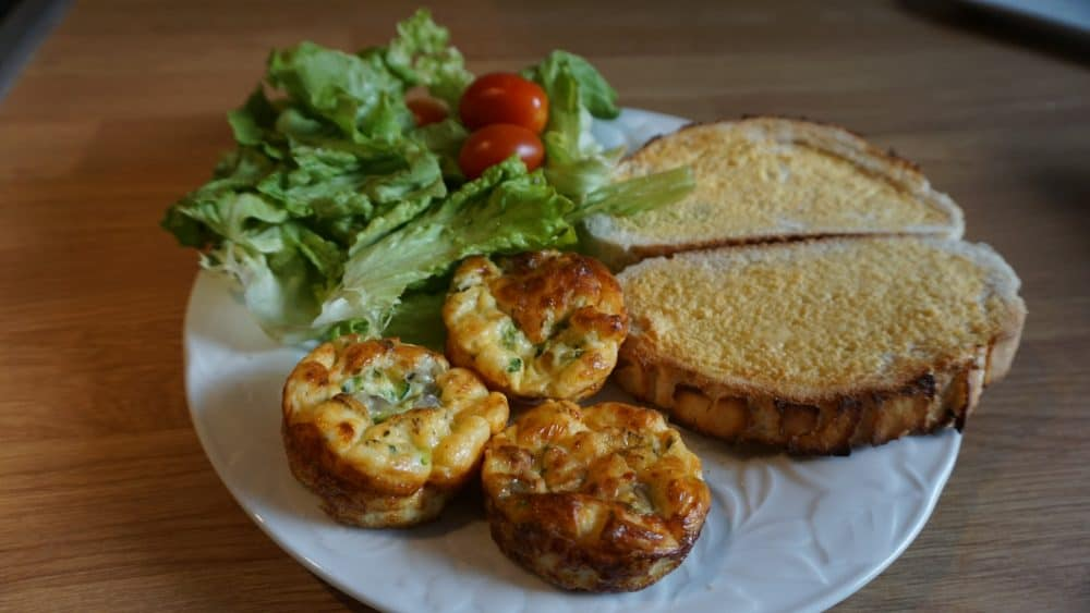 plate with courgette egg muffins, toast and salad
